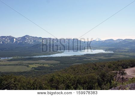 Summer. The mountain lake. The river results from lake. The blue sky.  The beautiful mountain landscape. The trees on declivity of the mountains. The Place attractive for tourism. The tranquil scene.