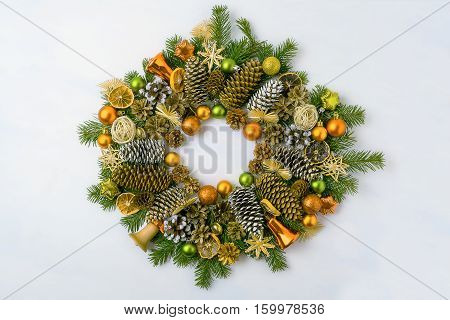Christmas wreath with fir branches pine cones and jingle bells. Christmas background with baubles jingle bells and dried orange slices.