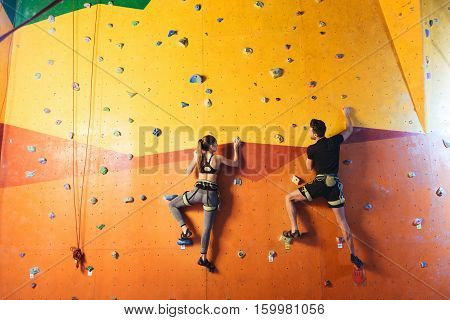 Couple activity. Overjoyed active young man and woman climbing up the wall while training and spending time together in climbing gym.
