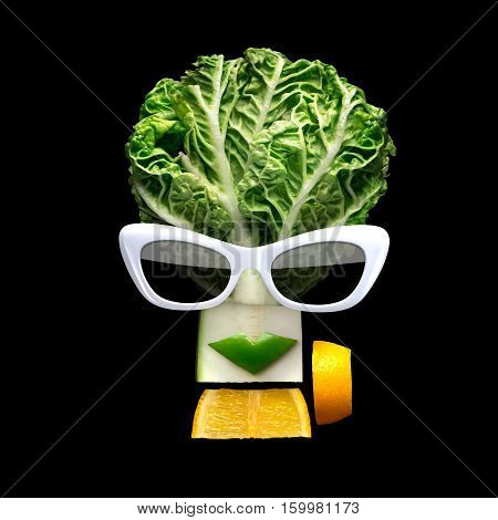 Quirky food concept of cubist style female face in sunglasses made of fresh fruits on black background.