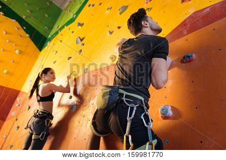 Fun and cooperation. Strong athletic young man and woman climbing up the wall while training and spending time climbing gym.