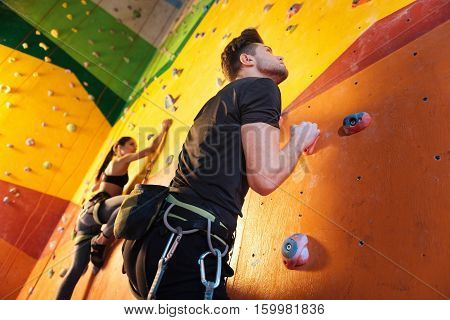 Good with you. Delighted athletic young couple climbing up the wall while training and holding hands in climbing gym.