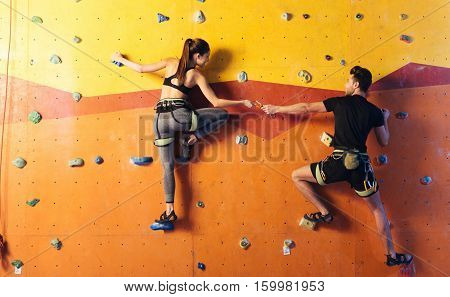 Lovely times. Joyful athletic young couple climbing up the wall together while training and holding hands in climbing gym.