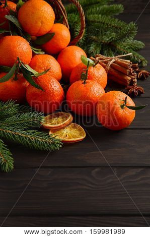 Fresh tangerine clementine with spices on dark wooden background, Christmas concept, selective focus, vertical, copy space