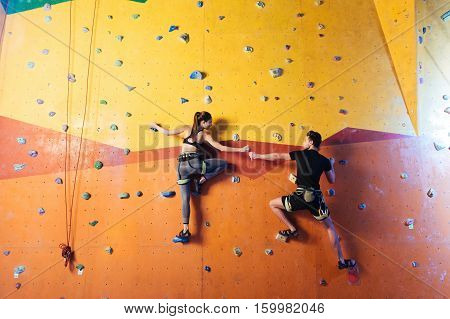 Full of joy. Happy athletic young couple climbing up the wall together while training and holding hands in climbing gym.