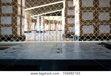empty black pallet in warehouse with stack of a several cartons background