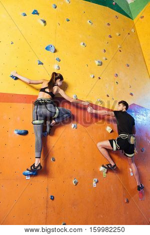 Amused and happy. Cute active young couple climbing up the wall together while training and holding hands in climbing gym.