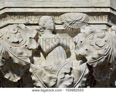 Woman pray at god as the sun in the sky symbolizes the hope. A medieval relief on Doge Palace outer portico in Venice