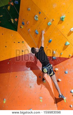 My lovely hobby. Young active delighted man training hard in climbing gym while using equipment and climbing up the wall.