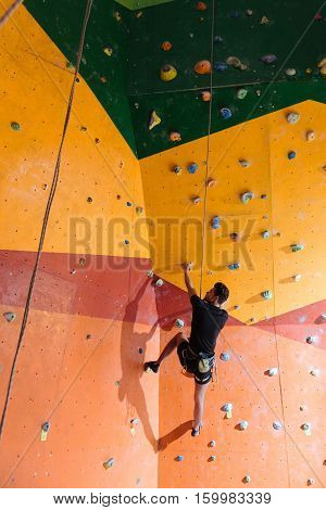 Best hobby. Happy active delighted man training hard in climbing gym while using equipment and climbing up the wall.