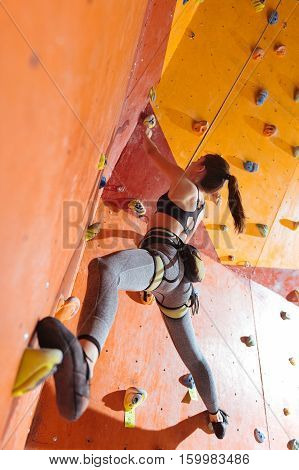 Female strength. Active delighted pretty woman training hard in climbing gym while using equipment and climbing up the wall.