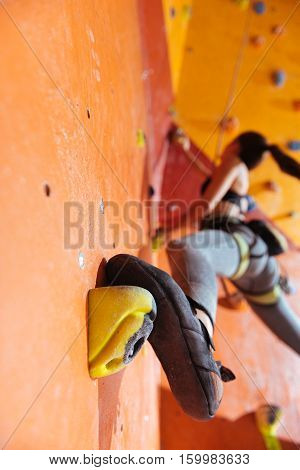 Female power. Athletic delighted pretty woman training hard in climbing gym while using equipment and climbing up the wall.