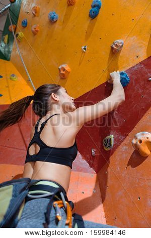 Keep fit and entertained. Slim young pretty woman training hard in climbing gym while using equipment and climbing up the wall.
