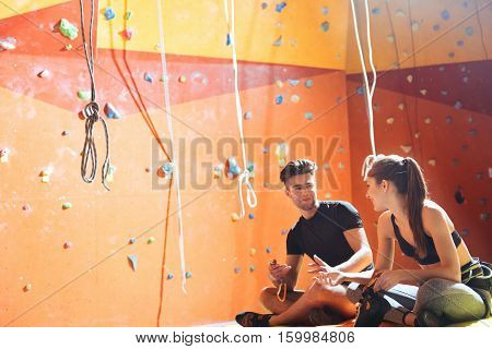 Common activity. Overjoyed young active couple sittiing in a climbing gym after training and climbing up the wall.