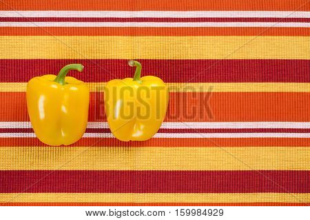 Healthy vegetables on the table covered with a tablecloth with stripes in the garden. Yellow peppers rich in vitamins are a very good choice for a healthy diet. Natural light and good mood.