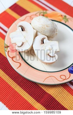 Healthy mushrooms on the table covered with a tablecloth with stripes in the garden. Raw mushrooms served on the plate hand-painted. Mushrooms are a good source of vitamins and a very good choice for a healthy diet. Natural light and good mood.
