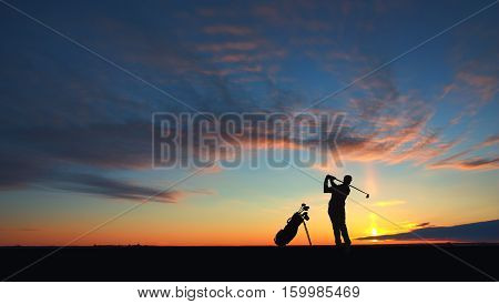 man golf player hit ball to air during sunset silhouetted