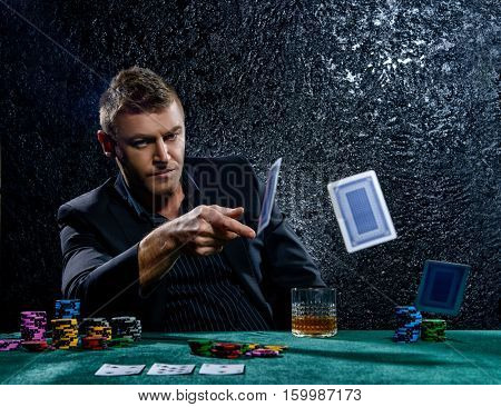 Excited gambling man throwing playing cards on a game table in a casino. Gambling, playing cards and roulette.