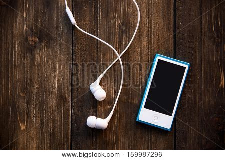 white earphones and blue music player on wooden background.