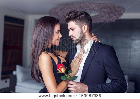 Young man give rose to lover indoor couple in love