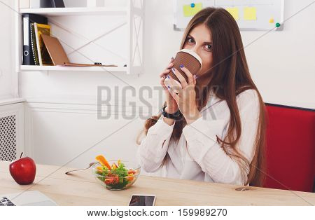 Woman has healthy business lunch in modern office interior. Young beautiful businesswoman at working place, eats vegetable salad in bowl, enjoys her coffee take away. Diet and vegetarian concept.