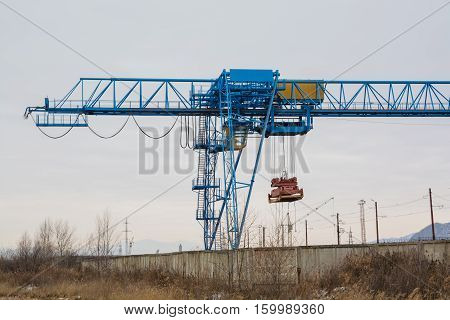 Blue gantry crane with winch over dull sky. Autumn day.