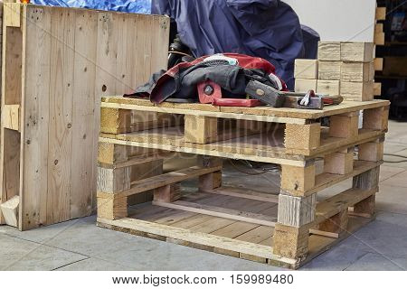 hammer, nippers tools and working cloth on wooden pallet. Wooden texture. Wooden background. How to make children bed from wooden pallets.