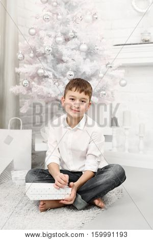 Preteen boy sitting in front of white christmas tree at home with gifts around.