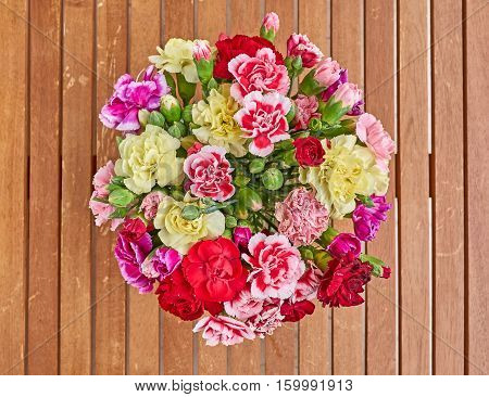 colorful carnation flowers bouquet on wooden background