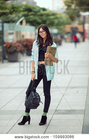 Confident asian student street portrait. Woman standing in full length outside with backpack and book in casual business suite against blurred city space. Beautiful young mixed race Asian Caucasian woman.