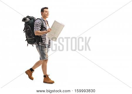 Full length portrait of a hiker walking and holding a generic map isolated on white background