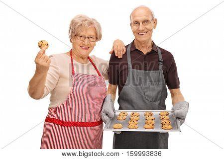 Elderly man holding a tray of freshly baked cookies and an elderly woman holding a single cookie isolated on white background