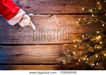 Christmas Santa Claus showing empty copy space by hand for text. Pointing finger, Proposing product. Advertisement gesture presenting point. Point to gift, text or product over wooden background