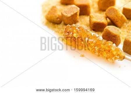 Brown amber sugar crystal on wooden stick and sugar cube isolated on white background.