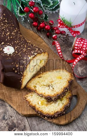 Chocolate yule log christmas cake and christmas ornament on wooden background