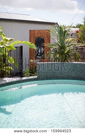 Modern swimming pool water close up beside a house with a fence and round and tile wall beside ornamental plants