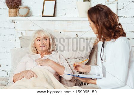 Urgent examination. Pleasant aged ill woman lying in bed and feeling ill while talking with her doctor at home