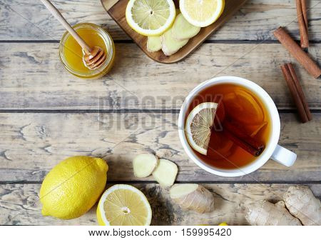 Antiviral useful drink ginger tea. Healthy drink. With lemon, honey and slices of ginger on wooden table. Top view. Rustic Style. Flat lay.