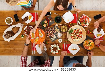 People eat healthy meals at festive table served for party. Friends celebrate with organic food on wooden table top view. Woman pass grilled corn dish to man