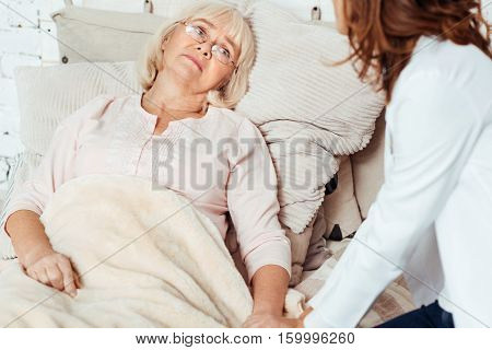Help me. Sick cheerless elderly woman lying in bed and feeling ill while professional doctor examining her at home