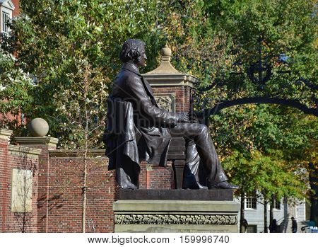 CAMBRIDGE USA - OCTOBER 20 2014: Statue of Charles Sumner in front of Harvard University entrance. Harvard is the most prestigious and oldest university in United States