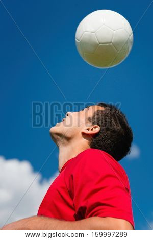 Soccer player bouncing ball, toned image, blue background
