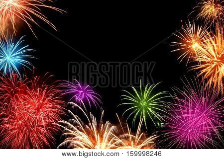 Gorgeous multi-colored fireworks as a border on black background ideal for New Year or other celebration events