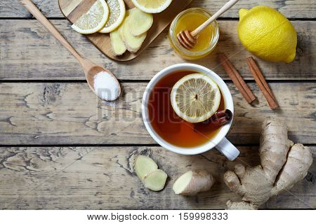 Cup of ginger tea with lemon and honey on wooden background. Top view. Antiviral Healthy drink useful tea. Creative composition.
