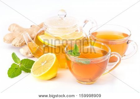 cup of hot tea and a teapot. ginger, lemon and mint on a white background