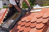 Hands of roofer laying tile on the roof. Installing natural red tile. poster