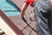 Roofer builder worker use a hammer for installing roofing shingles poster