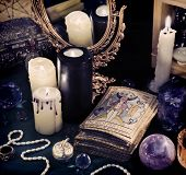 Black magic still life with the Tarot cards, mirror and crystal balls in candle light. Halloween concept, mystic fortune telling ritual, divination rite. Vintage objects on witch table poster