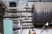 Hydraulic pipes an valves in basement. Home heating system in close up. poster