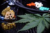 Medical marijuana products including cannabis leaf, dried bud, shatter piece, cbd caps and hash oil over black wood background poster